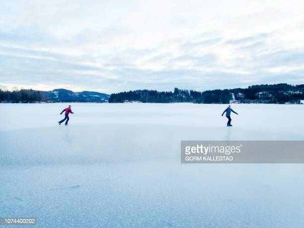 Two men skate on an icy lake as the Norwegian winter broke out in Trondheim Norway on December 19 2018 / Norway OUT