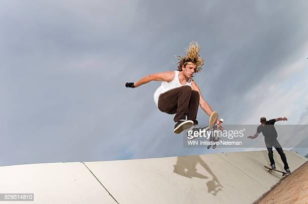 two men skateboarding on ramp - ハーフパイプ ストックフォトと画像