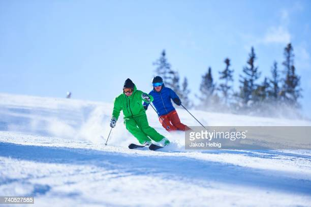 Two men skiing down snow covered ski slope, Aspen, Colorado, USA