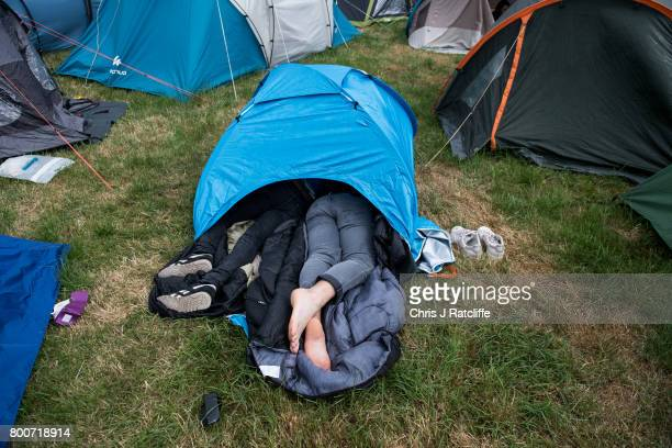 Two men sleep in a very small tent with their legs out stretching out of the door in a campsite at Glastonbury Festival Site on June 25 2017 in...