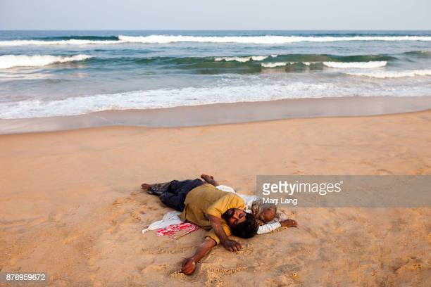 Two men sleeping on the sand by the ocean at Marina beach Chennai Tamil Nadu India