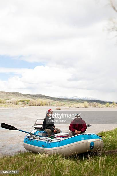 Two men smile while sitting on there raft in Montana.