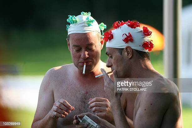 Two men smoke cigarettes after the freestyle competition of the waterballet event on the pink friday party of the Gay Games in the western German...