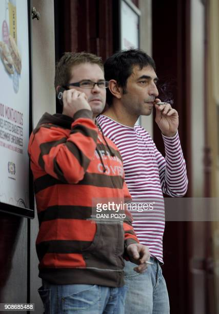 Two men smoke cigarettes outside a restaurant in Madrid on January 2 2011 A new Spanish antismoking law takes effect on January 2 prohibiting smoking...