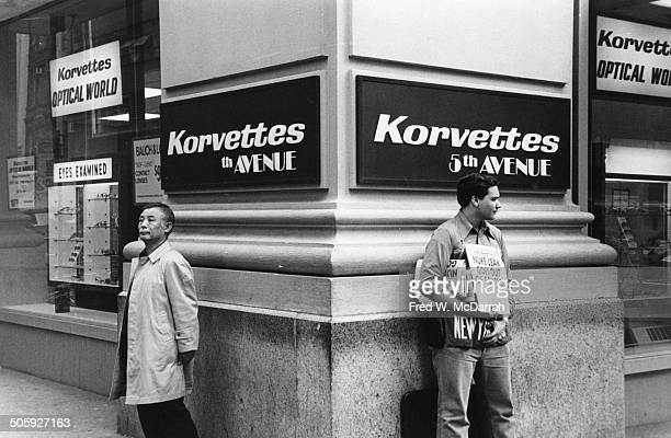 Two men stand against the wall of a Korvettes department store on the corner of 5th Avenue and W 47th Street New York New York March 28 1976 The man...