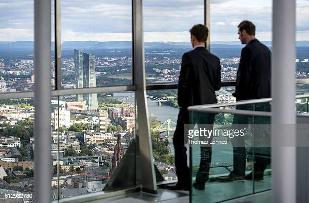 Two men stand at the viewing platform of the 'Maintower' and look to the headquarters of the European Central Bank on October 5 2016 in Frankfurt...