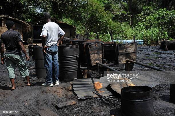 Two men stand beside local oil distillery mechanisms operated by oil thieves in Bayelsa State of the Niger Delta on April 11 2013 Shell Development...