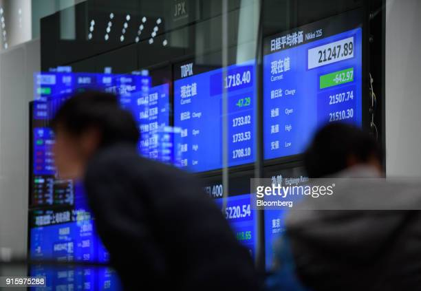 Two men stand in front of a screen displaying stock indices at the Tokyo Stock Exchange , operated by Japan Exchange Group Inc. , in Tokyo, Japan, on...