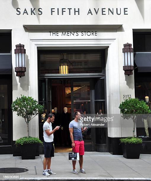 Two men stand in front of the Saks Fifth Avenue Men's Store in San Francisco's upscale Union Square shopping area on September 30 2013 in San...