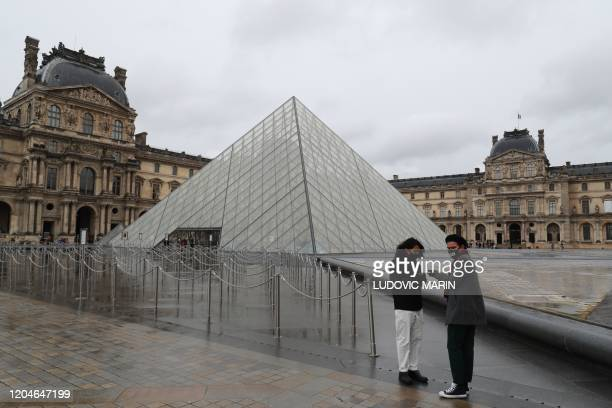 Two men stand in the deserted court yard outside the closed Pyramid, the main entrance to the Louvre museum which was once a royal residence, located...