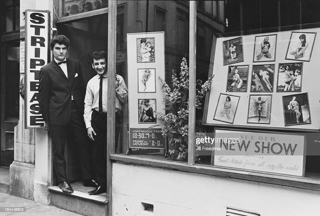 Two men stand in the doorway of a Soho strip club, London, circa 1969.