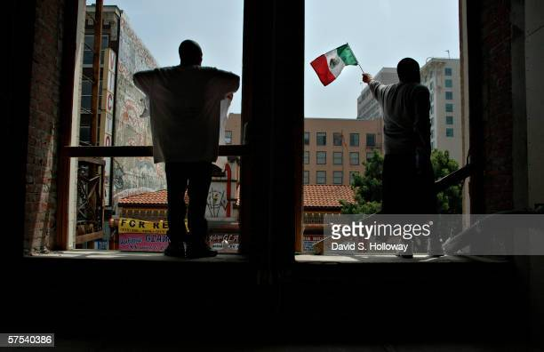 Two men stand in the windows of a construction site as hundreds of thousands of immigrants demonstrate on May 1 2006 in downtown Los Angeles...