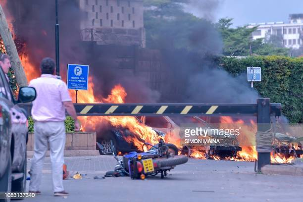 Two men stand next to burning cars at the scene of an explosion at a hotel complex in Nairobi on January 15 2019 A blast at the DusitD2 compound...