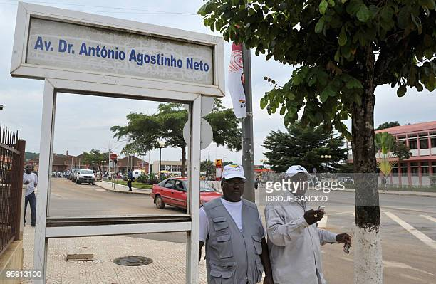 Two men stand on the Avenue Dr Antonio Agostinho Neto of the 2010 African Cup of Nations football tournament near a building on January 20 2010 in...