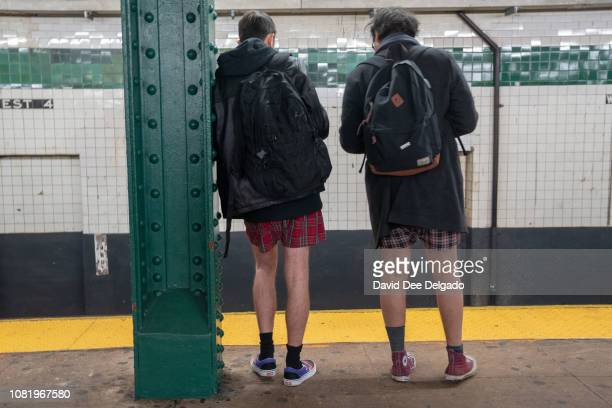 Two men stand on the platform of the West 4th, F subway line during the 18th annual No Pants Subway Ride on January 13, 2019 in New York City. 24...