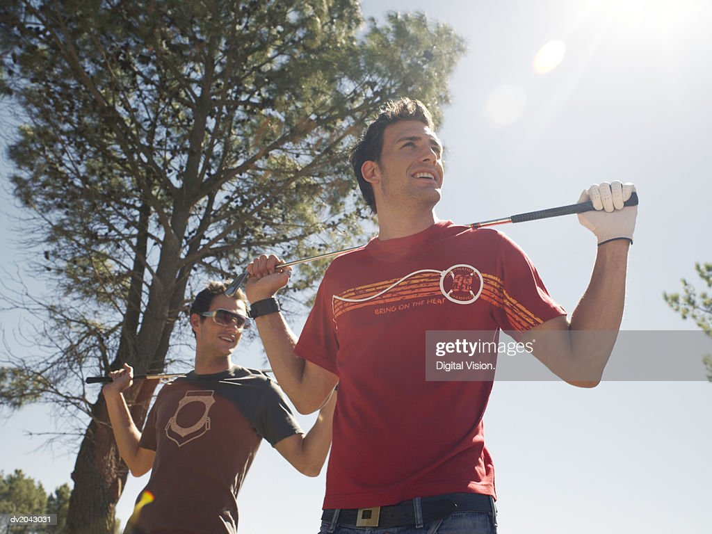 Two Men Stand Outdoors Carrying Golf Clubs on Their Shoulders : Stock Photo