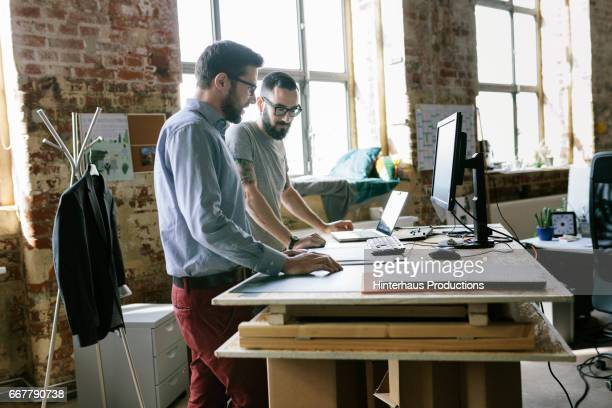 Two men standing at a makeshift desk