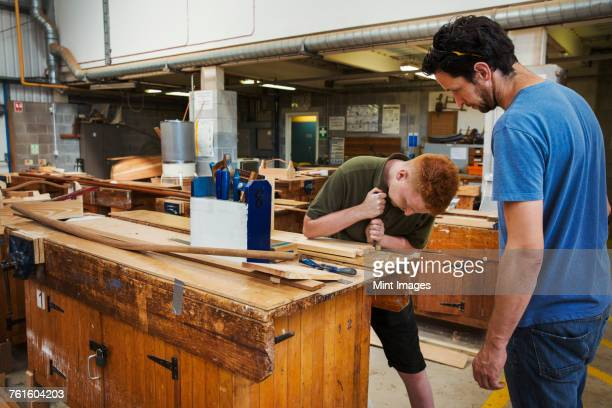 Two men standing at a workbench in a boat-builders workshop, working on wooden joint.