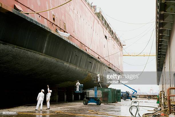 two men standing at base of ship in shipyard - cantiere navale foto e immagini stock
