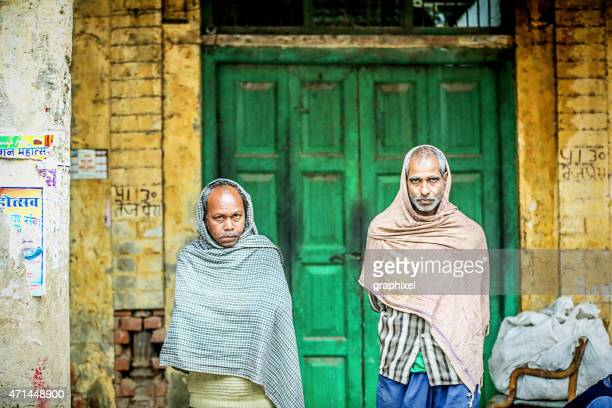 two men standing at entrance of street market - graphixel stock pictures, royalty-free photos & images