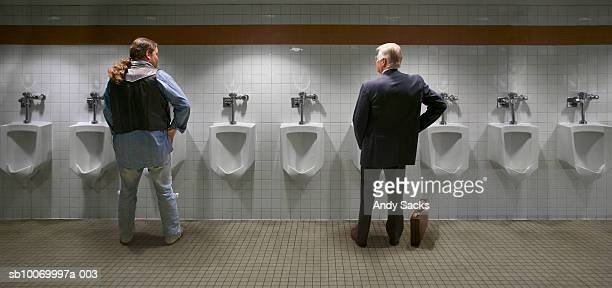 Two men standing at urinal, rear view (digital composite)