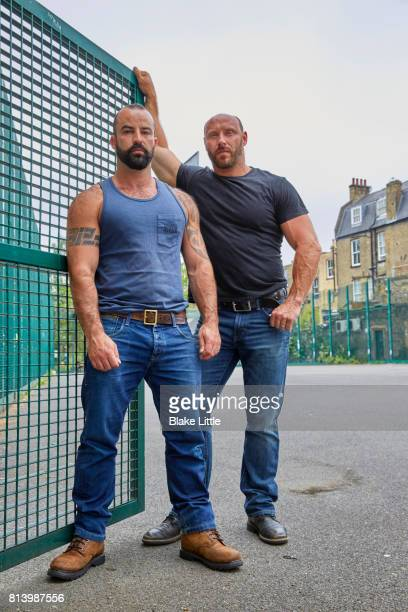 two men standing by fence - black boot stock pictures, royalty-free photos & images