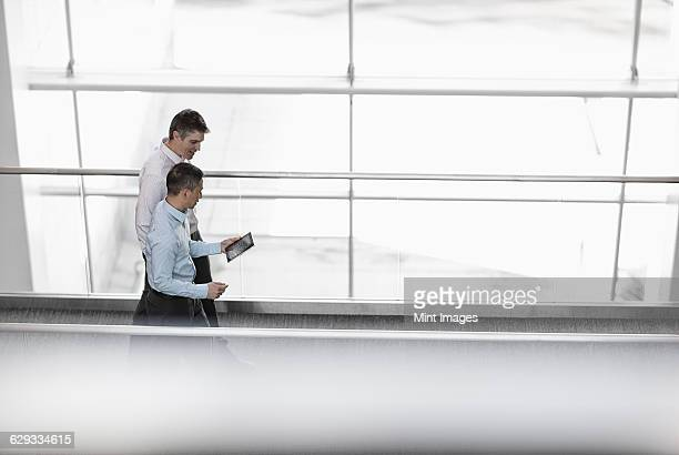 Two men standing by the large windows of a building, looking at the screen of a digital tablet.