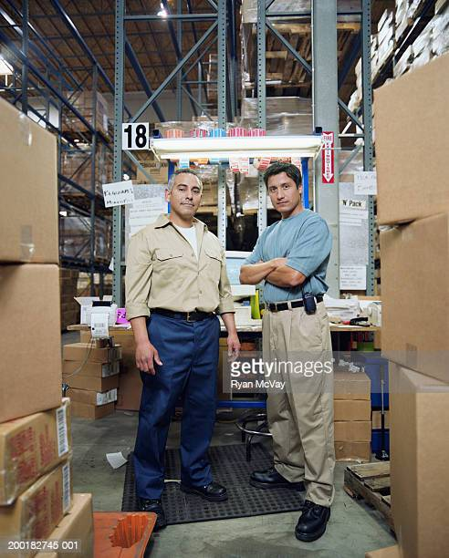Two men standing by workstation in warehouse, portrait