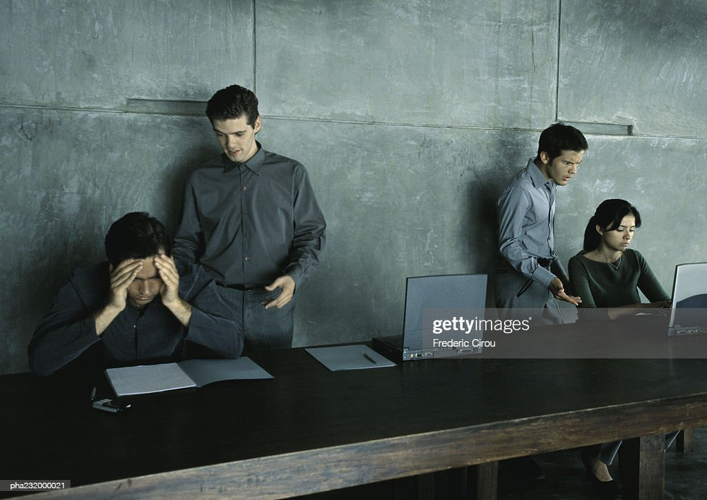 Two men standing helping man and woman sitting at table. : Stockfoto