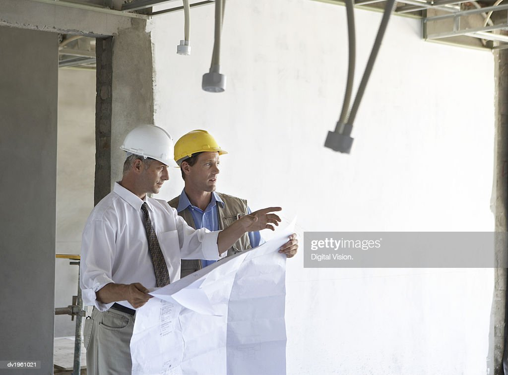 Two Men Standing in a Partially Constructed Room, Holding Blueprints : Stock Photo