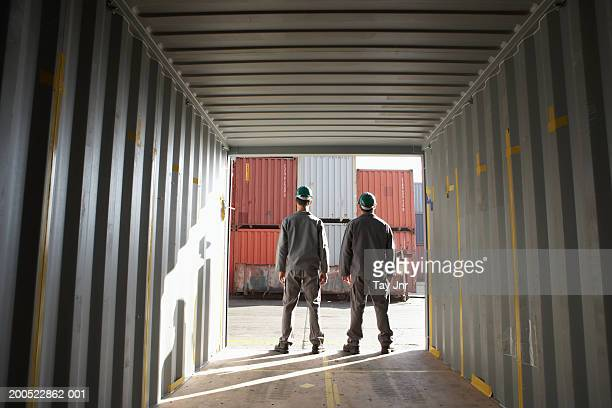 Two men standing in cargo container, looking out, rear view