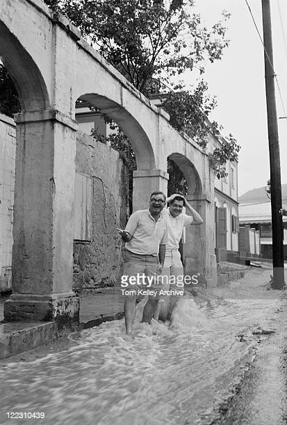 Two men standing in flowing water, smiling