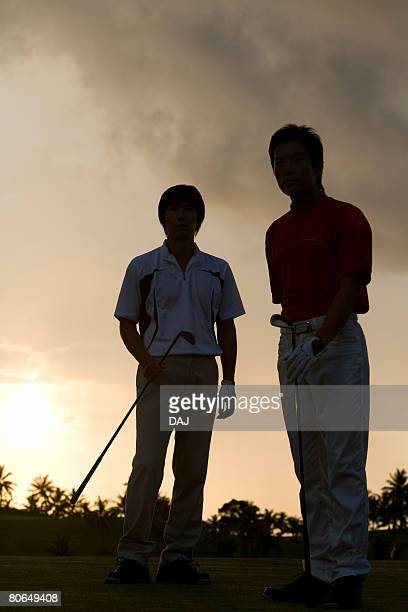 Two Men Standing in Golf Links, Holding Golf Clubs, Sunset Behind the Men