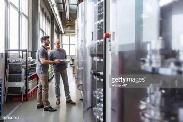 Two men standing in modern factory