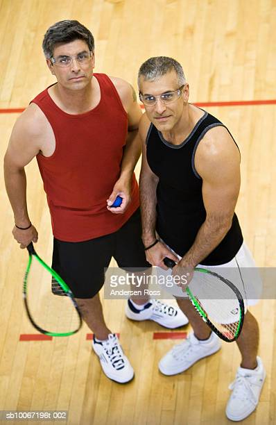 Two men standing in squash court, portrait, elevated view
