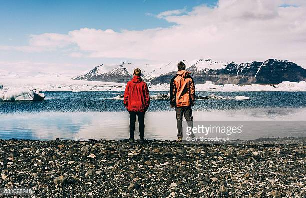 Two men standing near the lake with glaciers