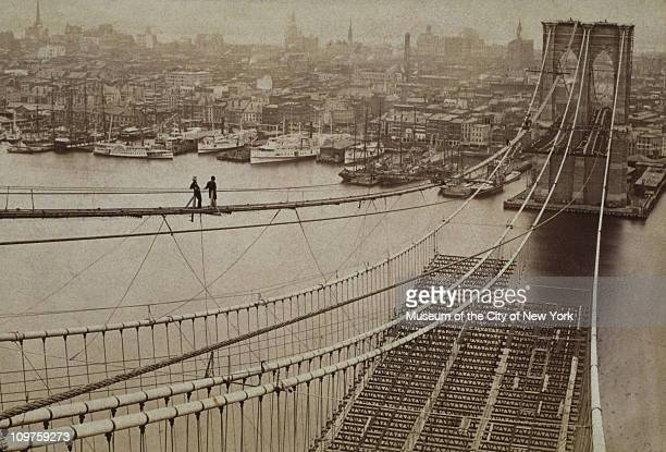 Two men standing on a high catwalk surveying the construction of the Brooklyn Bridge with Manhattan in the background New York City 1877 The roadway...