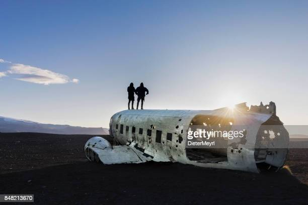 two men standing on airplane wreck - solheimasandur iceland - westfjords iceland stock photos and pictures