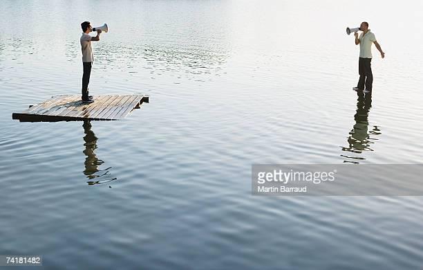 Two men standing on water with megaphones