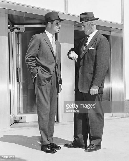 Two men standing, one checking watch