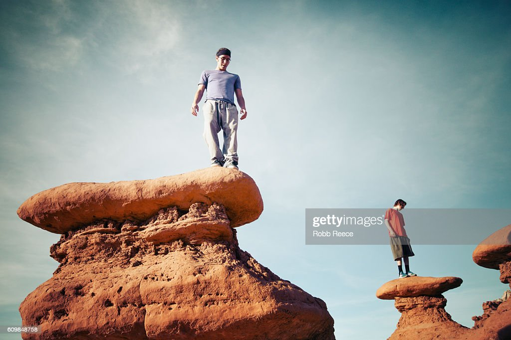 Two men standing outdoors on rock formations in the desert : Stock Photo