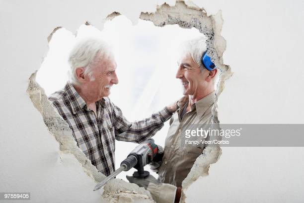 Two men standing outside hole in wall