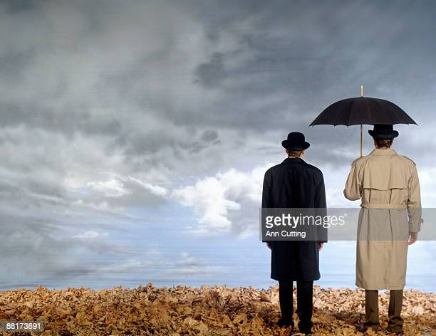 Two men standing side by side in field , one with an umbrella