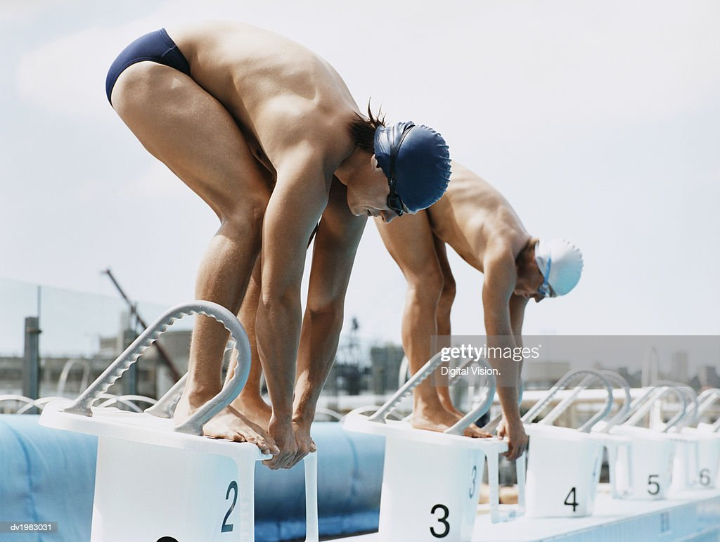 Two Men Standing Side by Side on Starting Blocks at a Swimming Pool : Stock Photo