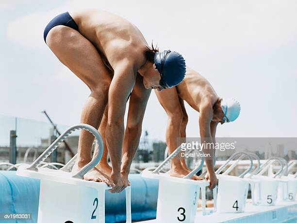 Two Men Standing Side by Side on Starting Blocks at a Swimming Pool