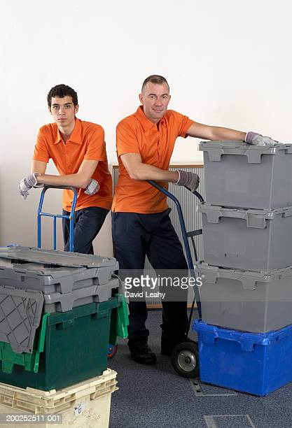 Two men standing with crates on sack barrows, portrait