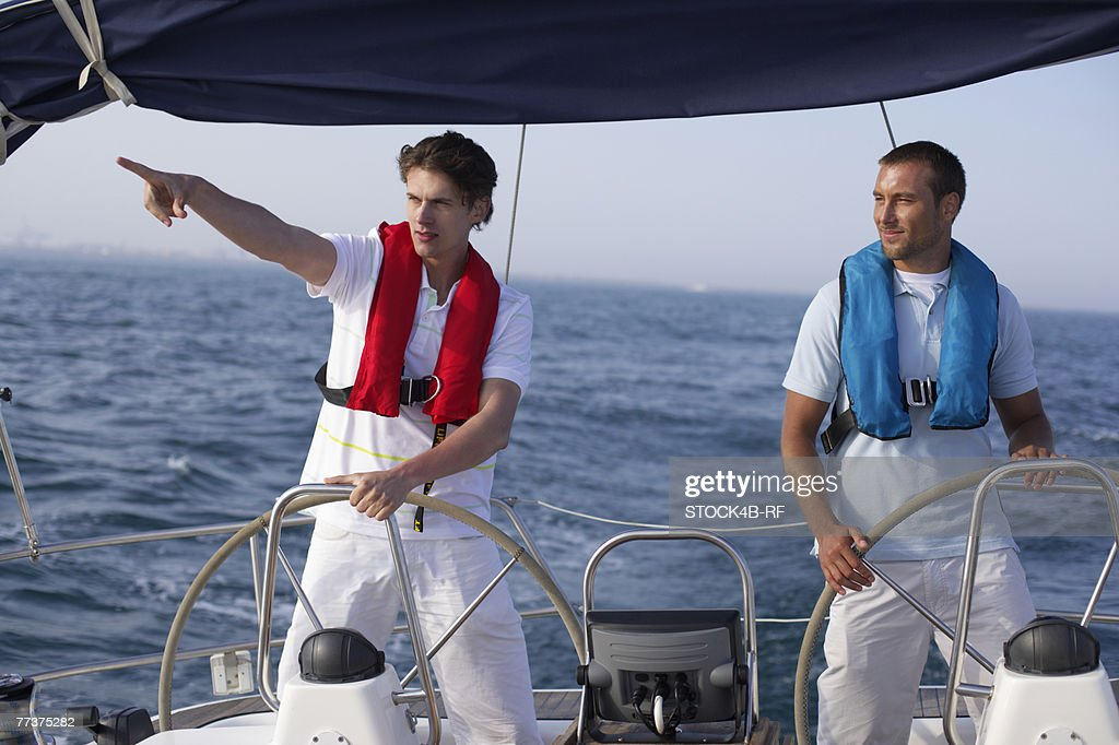 Two men steering a boat : Photo