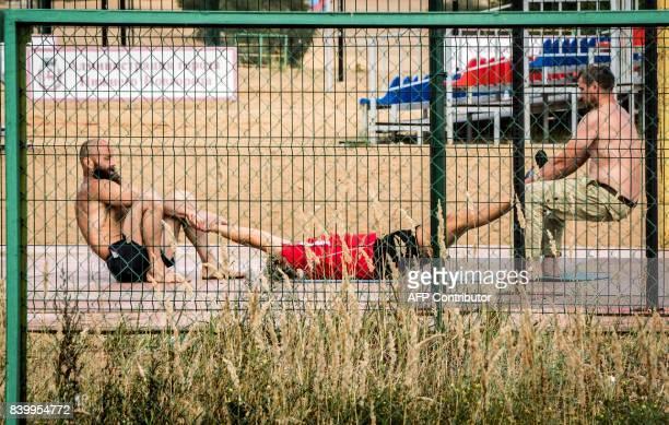 TOPSHOT Two men strech their friend as they exercise in a sport field in Nizhny Novgorod on August 26 2017 Nizhny Novgorod will host several games of...