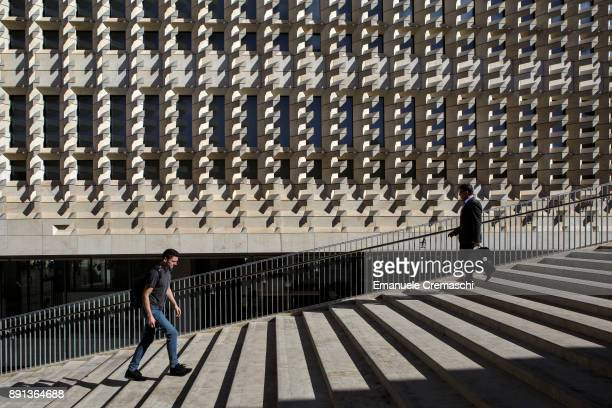 Two men stroll past the limestone steps of Valletta's Parliament designed by Italian architect Renzo Piano on December 7 2017 in Valletta Malta...