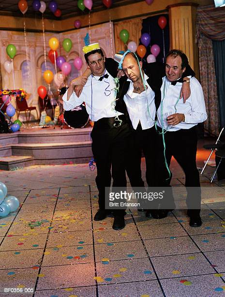 two men supporting drunken man at party - binge drinking stock pictures, royalty-free photos & images